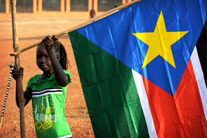 A South Sudanese girl holding a South Sudanese flag
